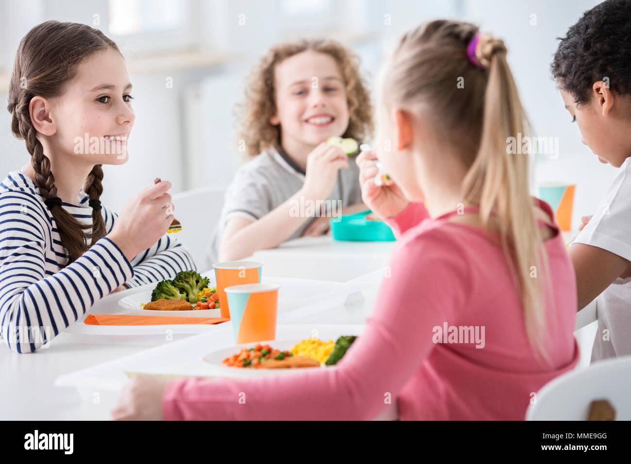 Lächelnde Mädchen essen Gemüse während der Mittagspause mit Freunden in der Schule Stockbild