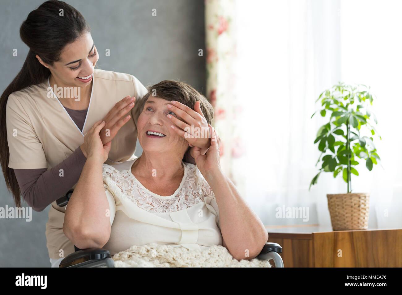 Enkelin Freiwilligenarbeit in einem Seniorenheim überraschend ihre Großmutter, die nach der Arbeit Stockbild