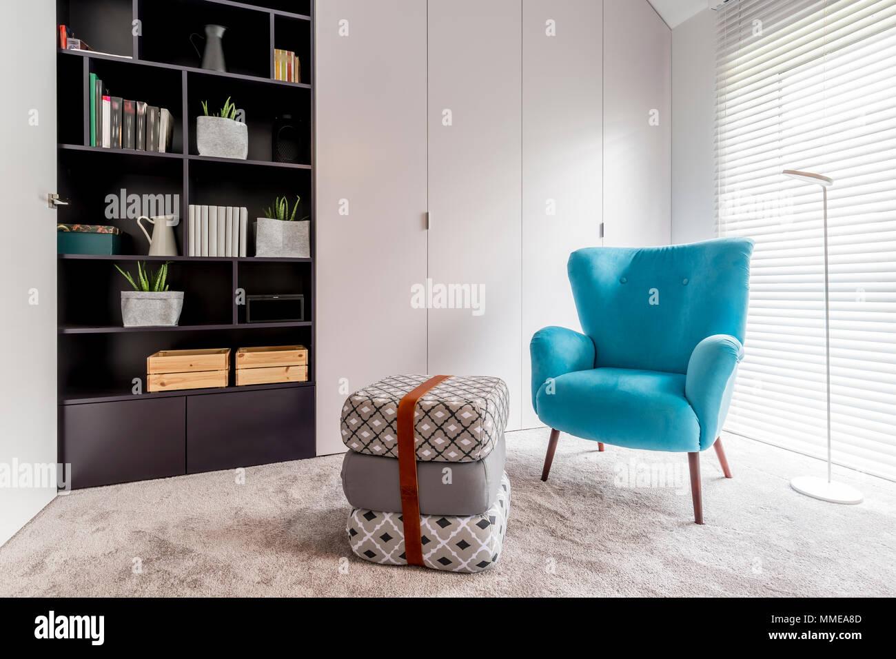 Modernes Interieur mit gemütliche Leseecke mit schwarzen Bücherregal ...
