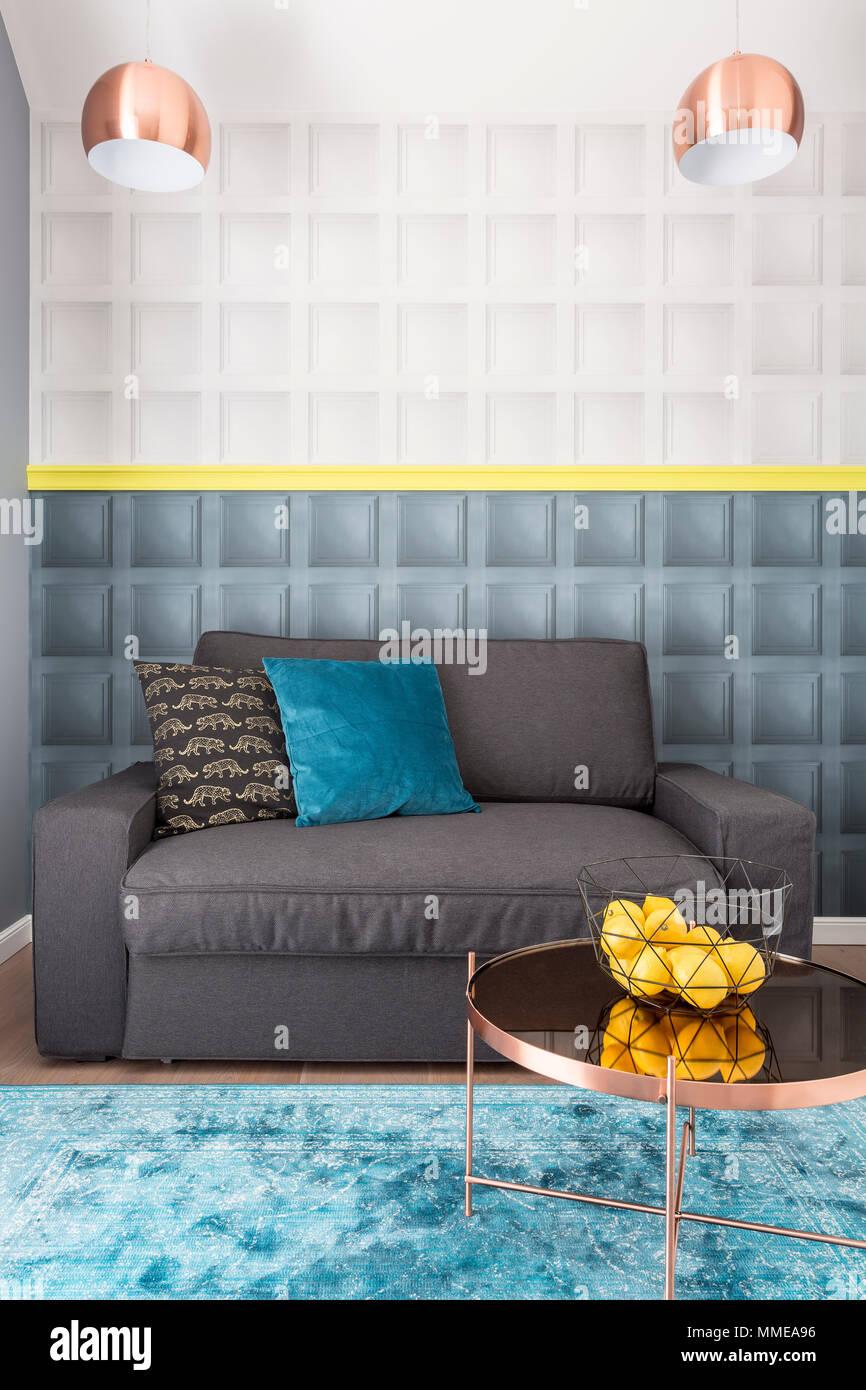 Wohnzimmer Einrichtung In Eleganten Stil Mit Kupfer Couchtisch, Lampen Und  Dekorative Schwarze Und Blaue Kissen Auf Gemütlichen Grau Sofa