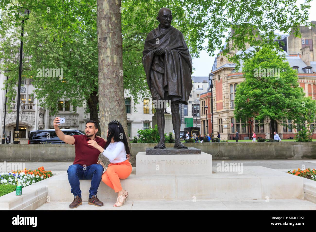 Westminster, London, 11. Mai 2018. Ein paar nehmen selfies vor dem Mahatma Gandhi Statue in Parliament Square. Trotz der bewölkt und etwas kältere Wetter, Touristen um Westminster und South Bank sind in großen Zahlen genießen Sie die Sehenswürdigkeiten der britischen Hauptstadt. Credit: Imageplotter Nachrichten und Sport/Alamy leben Nachrichten Stockfoto