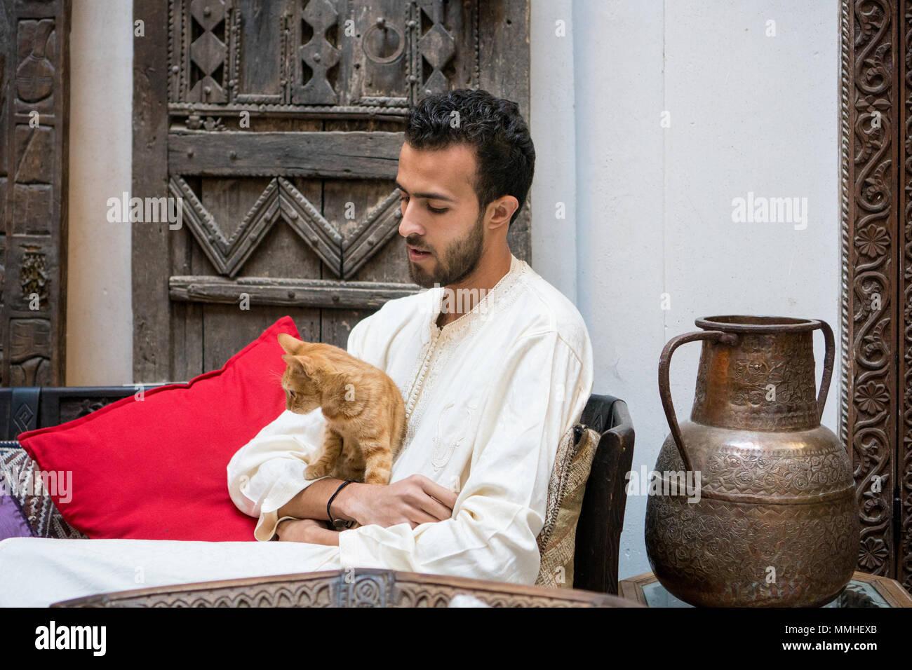 Junge muslimische Mann hält eine gelbe Katze vor einem geschmückten Wand Stockbild
