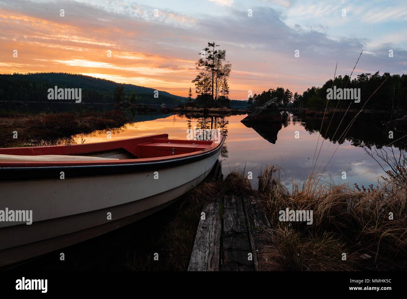 Boot bereit für die Fischerei in einem ruhigen See mit einem schönen Sonnenuntergang in Schweden Mai 2018 Stockbild