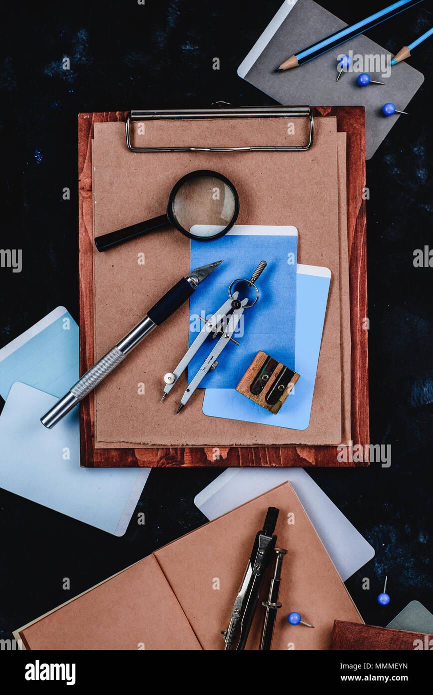 Holz- Zwischenablage mit Handwerk Papier und Skizzen auf einen Designer Arbeitsplatz hautnah. Skizzen, Kompasse, Herrscher und Bleistifte in ein Architekt oder Innenraum d Stockbild