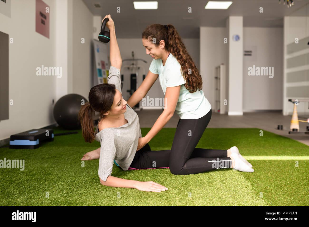 Physiotherapeuten Unterstützung von jungen kaukasischen Frau mit Übung mit Hantel während der Rehabilitation in der Turnhalle am Krankenhaus. Weibliche Physiotherapeut tr Stockbild