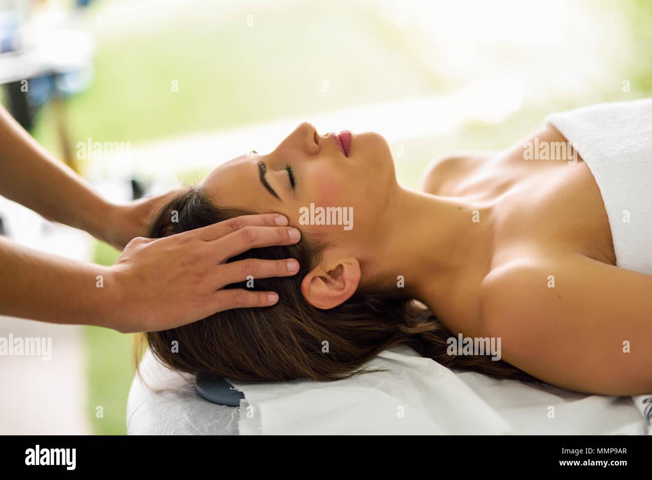 Junge kaukasier lächelnde Frau mit einem Kopf Massage im Spa Center mit geschlossenen Augen. Weibliche Patienten ist, die Behandlung von professionellen therapi Stockbild