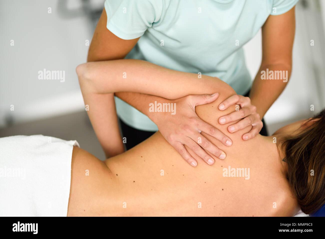 Professionelle female Physiotherapeut die Schulter Massage Frau im Krankenhaus zu brunette. Medizinische Check an der Schulter in der Physiotherapie. Stockbild