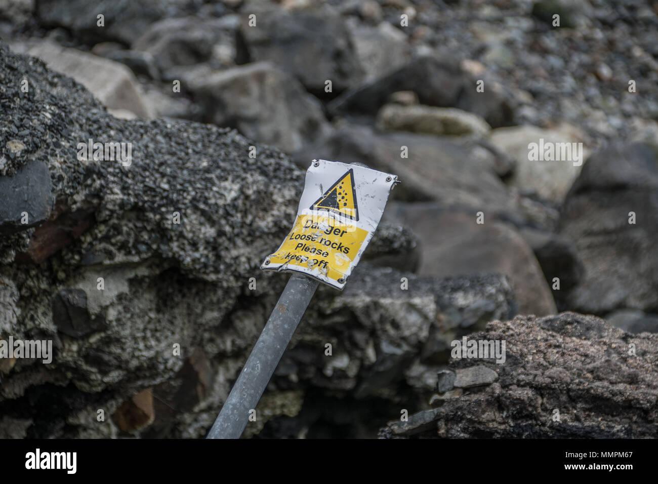 Gefahr lose Felsen Zeichen, verbogen worden ist und ein Umkippen vor einige lose Felsen an der Küste in Newlyn in Cornwall. Stockbild