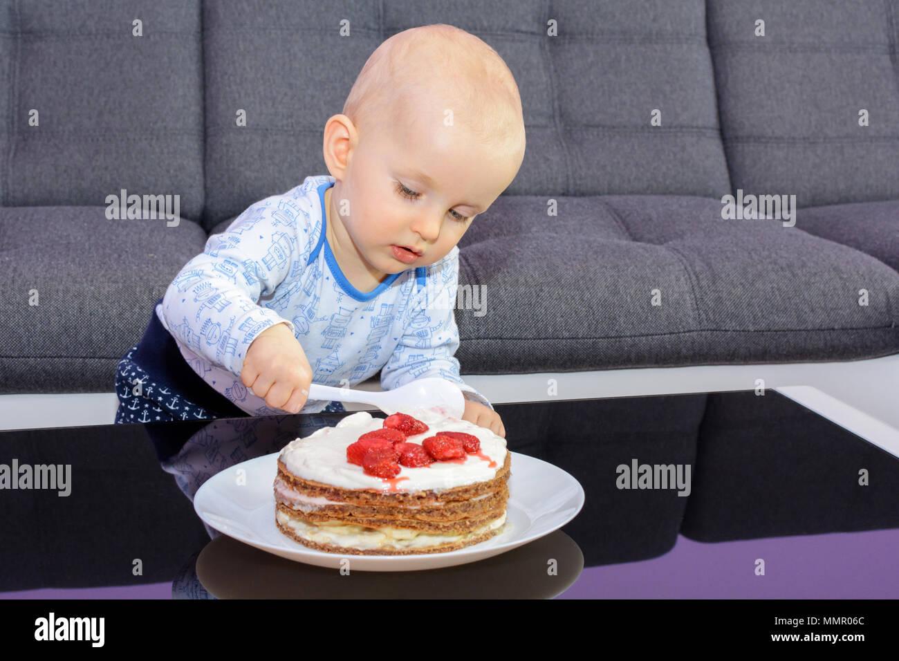 Der erste Geburtstag Feier eines kleinen Jungen. Little Boy essen Geburtstag Kuchen mit einem Löffel, alles Gute zum Geburtstag. Kleinkind am Tisch mit Kuchen. Stockfoto