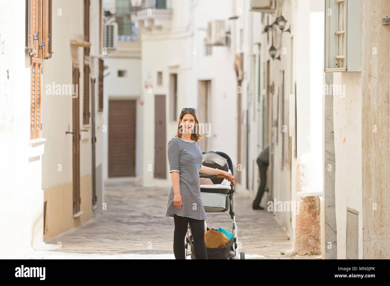 Gallipoli, Apulien, Italien - eine Frau mit einem Kinderwagen in einem mittleren Alter Gasse Stockfoto