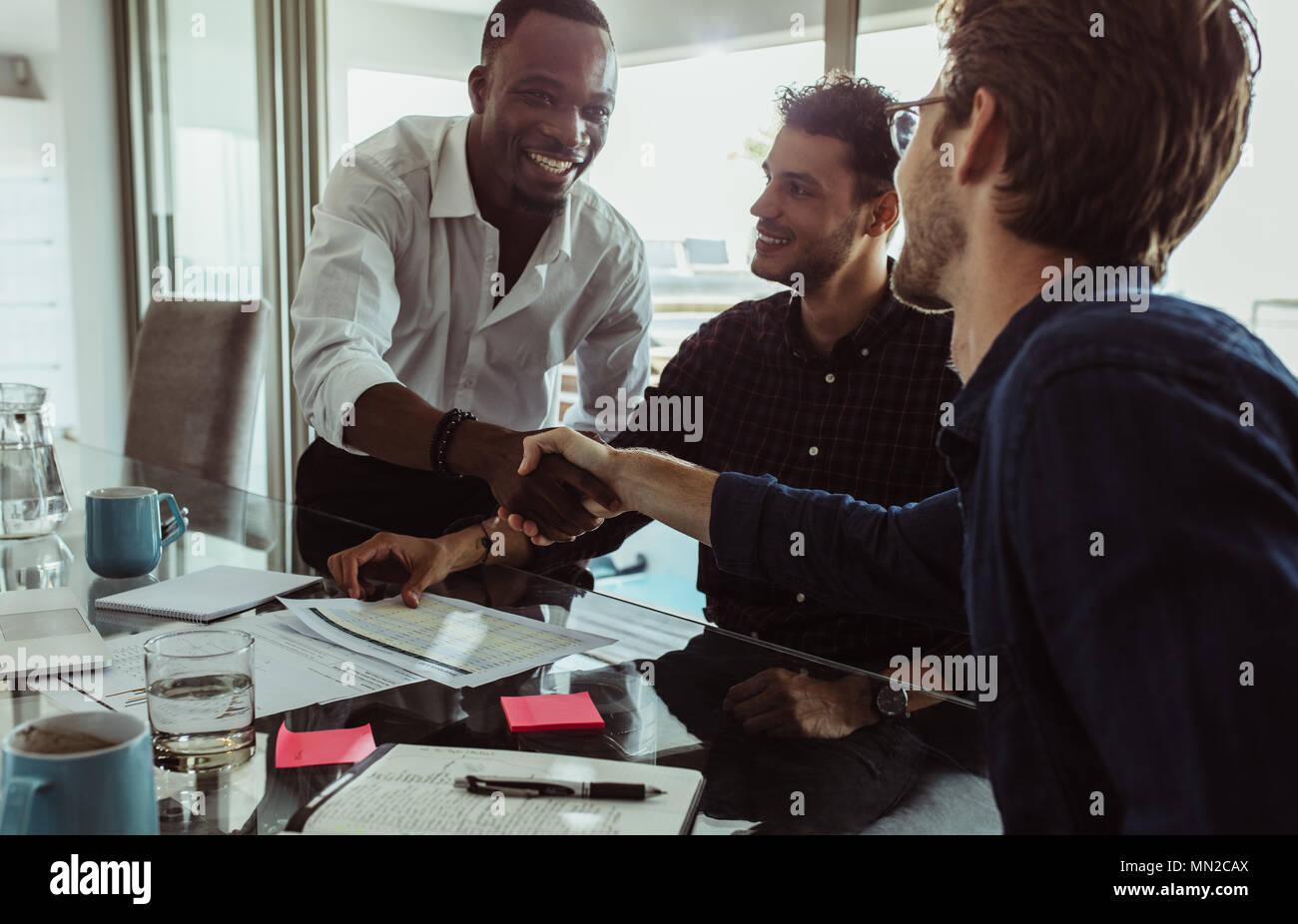Unternehmer diskutieren Arbeit am Konferenztisch Sitzen im Büro. Männer die Hände schütteln und lächelnd während einer Konferenz. Stockbild