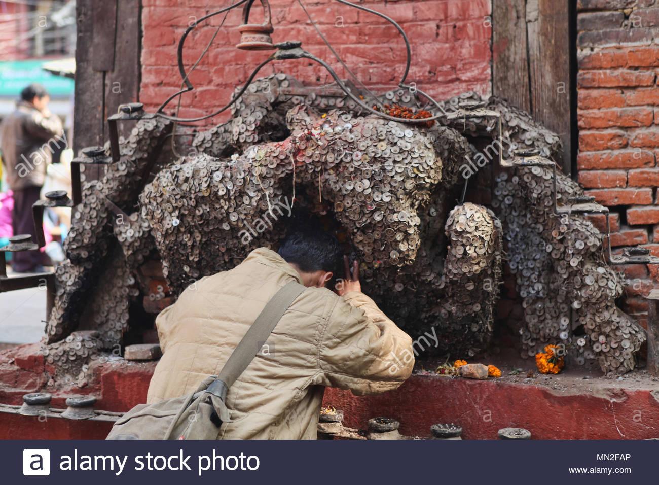 Ein Mann bietet, ein Gebet zu dem Gott seine Zahnschmerzen Zahnschmerzen in Kathmandu, Nepal zu lindern. Nach dem Hämmern ein Nagel mit einer Münze in den Schrein und der Stockbild