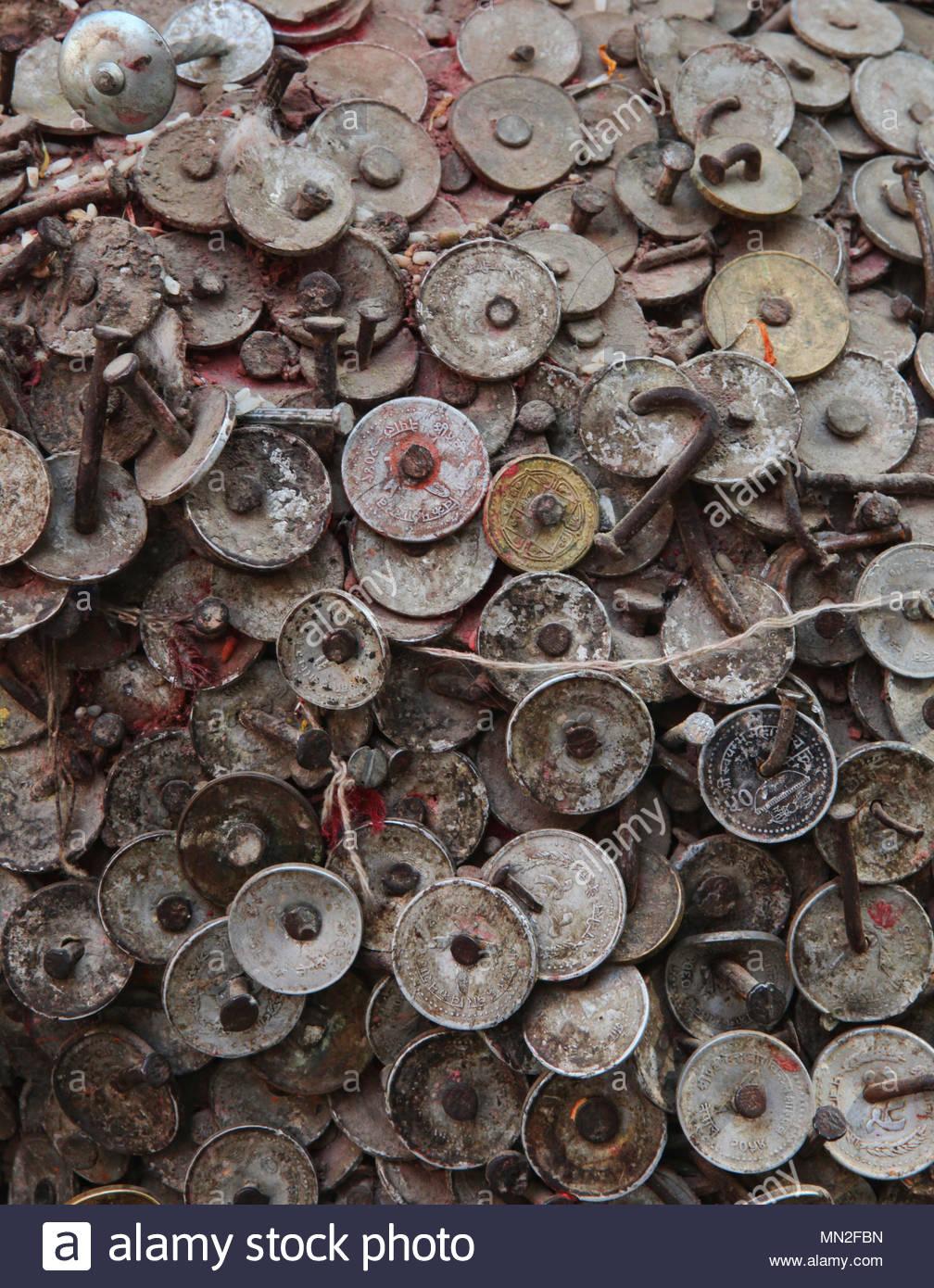 Nahaufnahme der Münzen an den Glanz der Zahnschmerzen Gott in Kathmandu, Nepal genagelt. Nach dem Hämmern ein Nagel mit einer Münze in den Schrein und Gebet Stockbild