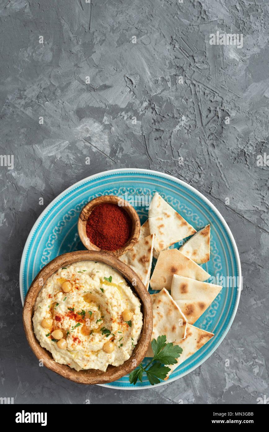 Kichererbse Hummus und Pita Chips auf konkreten Hintergrund. Ansicht von oben mit der Kopie Platz für Text. Arabisch, libanesisch, vegan und vegetarisch Dip oder Snack Stockbild