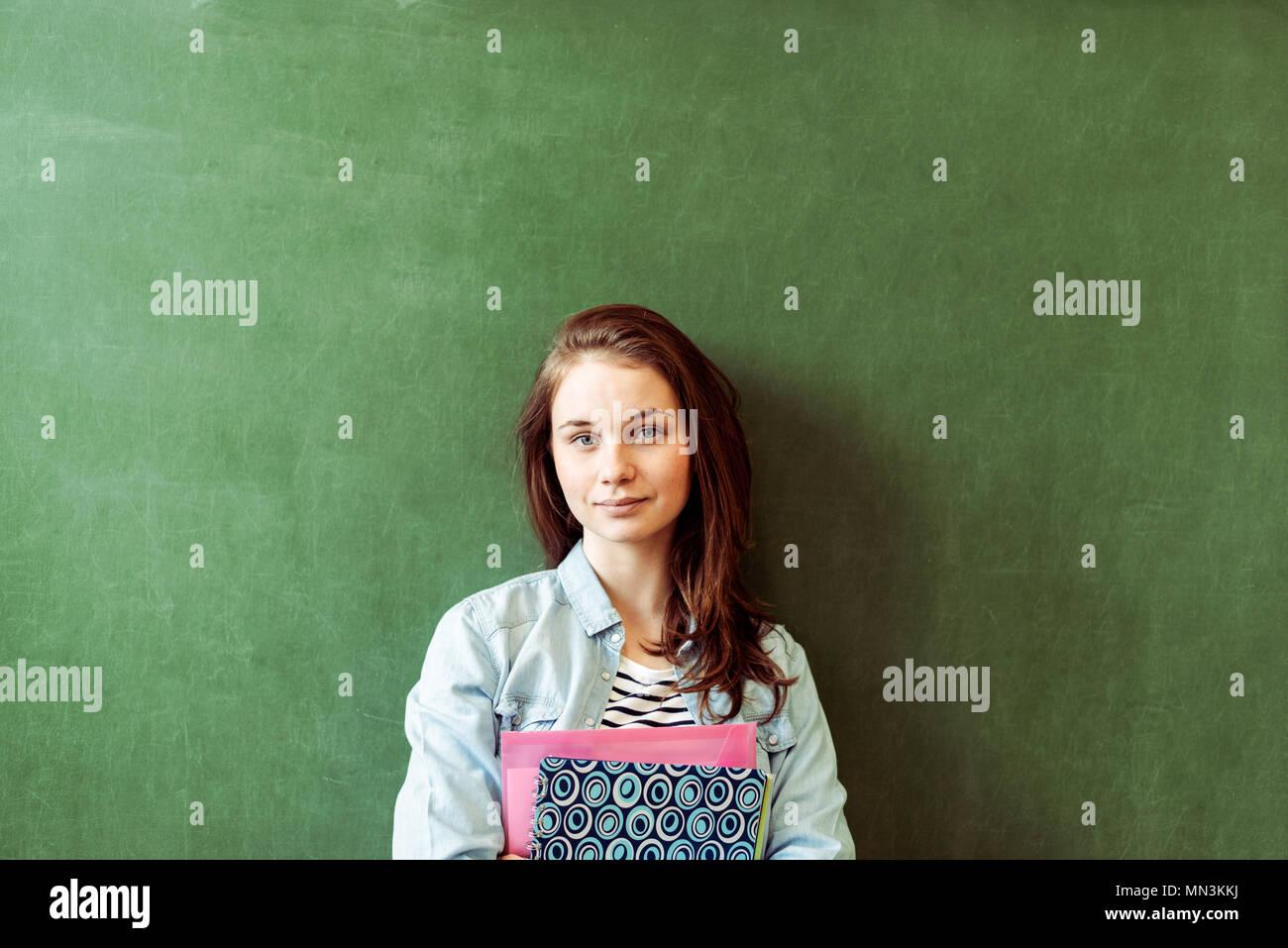 Junge zuversichtlich lächelnd weibliche Schüler vor der Tafel im Klassenzimmer, die hielten Lehrbücher, bei Kamera schaut. Stockfoto