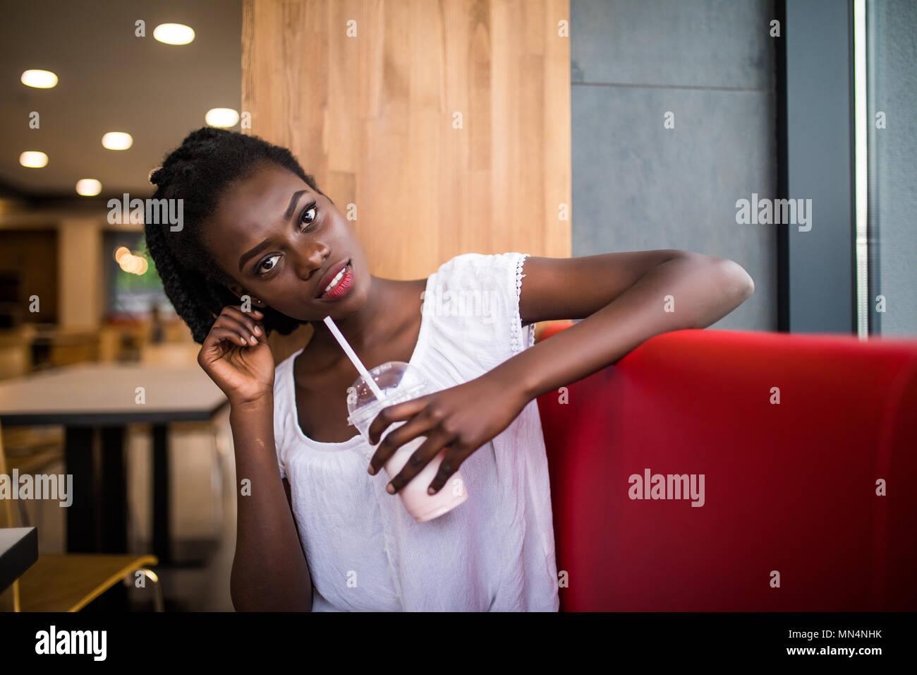Foto von positiven dunkelhäutige Afro-amerikanische Frauen ejoys gute Erholung im Coffee Shop, Getränke trinken. Menschen, Freizeit und Essen Konzept Stockbild