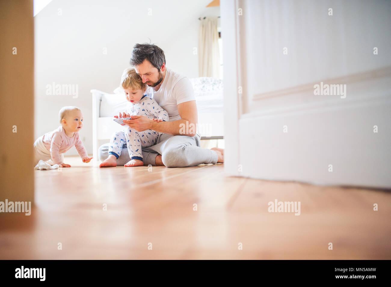 Fußboden Günstig Urlaub ~ Vater und kind kinder mit smartphone auf dem fußboden sitzen zu