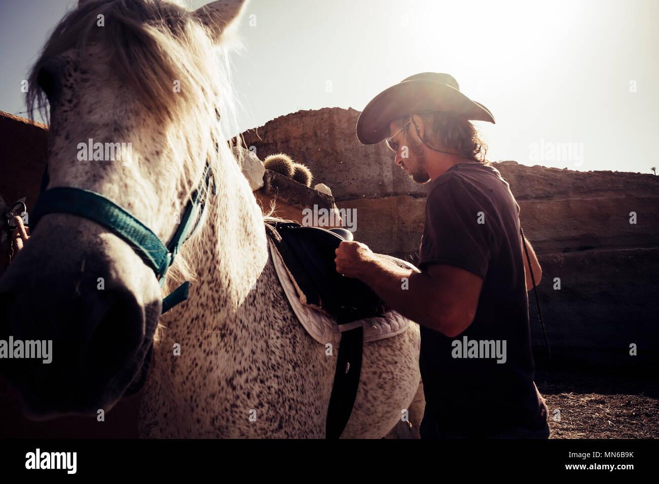 Schönen cowboy Szene mit Bergen im Hintergrund und die Hintergrundbeleuchtung vom Sonnenuntergang für schöne junge Mann blonde lange Haare und bester Freund Pferd t Stockbild