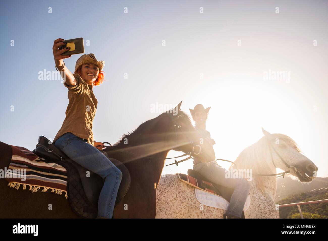 Paar auf Pferden reiten im Freien unter der Sonne im Gegenlicht für Freizeit Aktivitäten selfie mit modernen Mobilfunktechnologie. Alternative li Stockbild