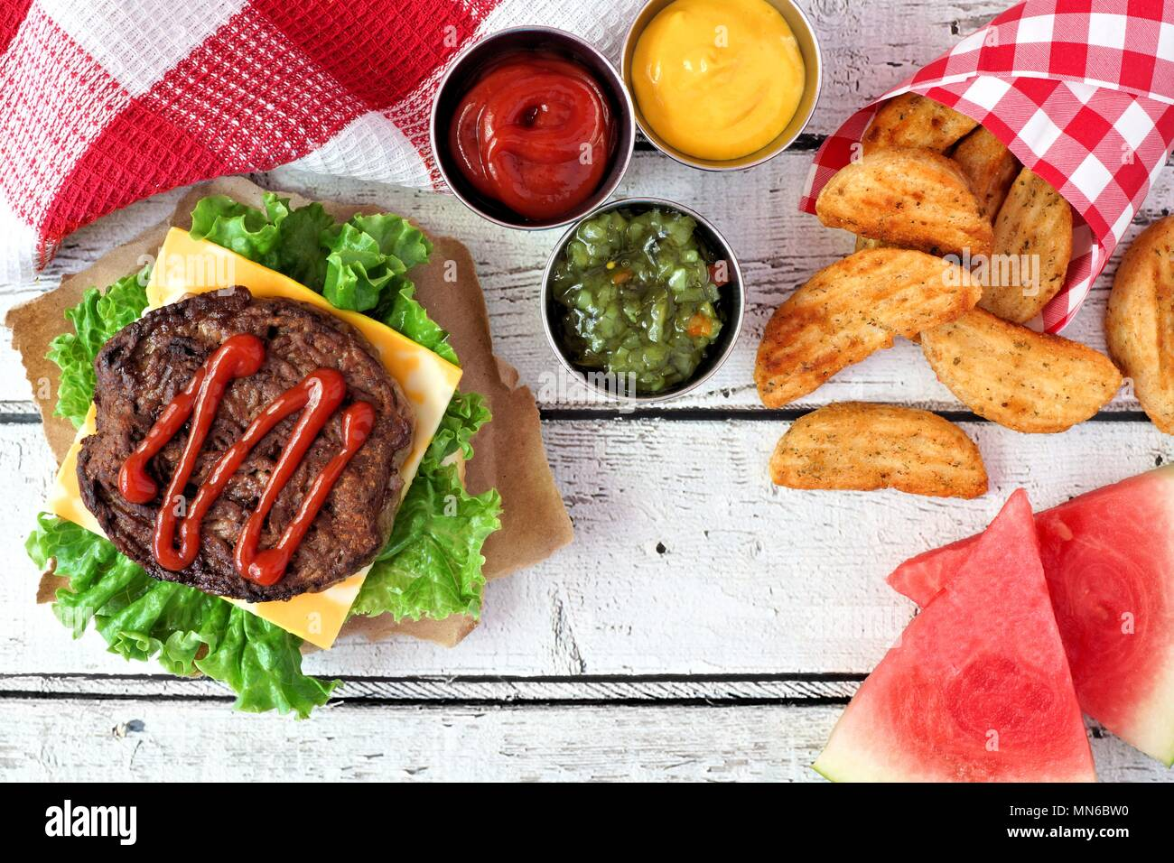 Picknick Szene mit offenen Hamburger, Wassermelone und Potato Wedges auf weißem Holz Hintergrund Stockbild