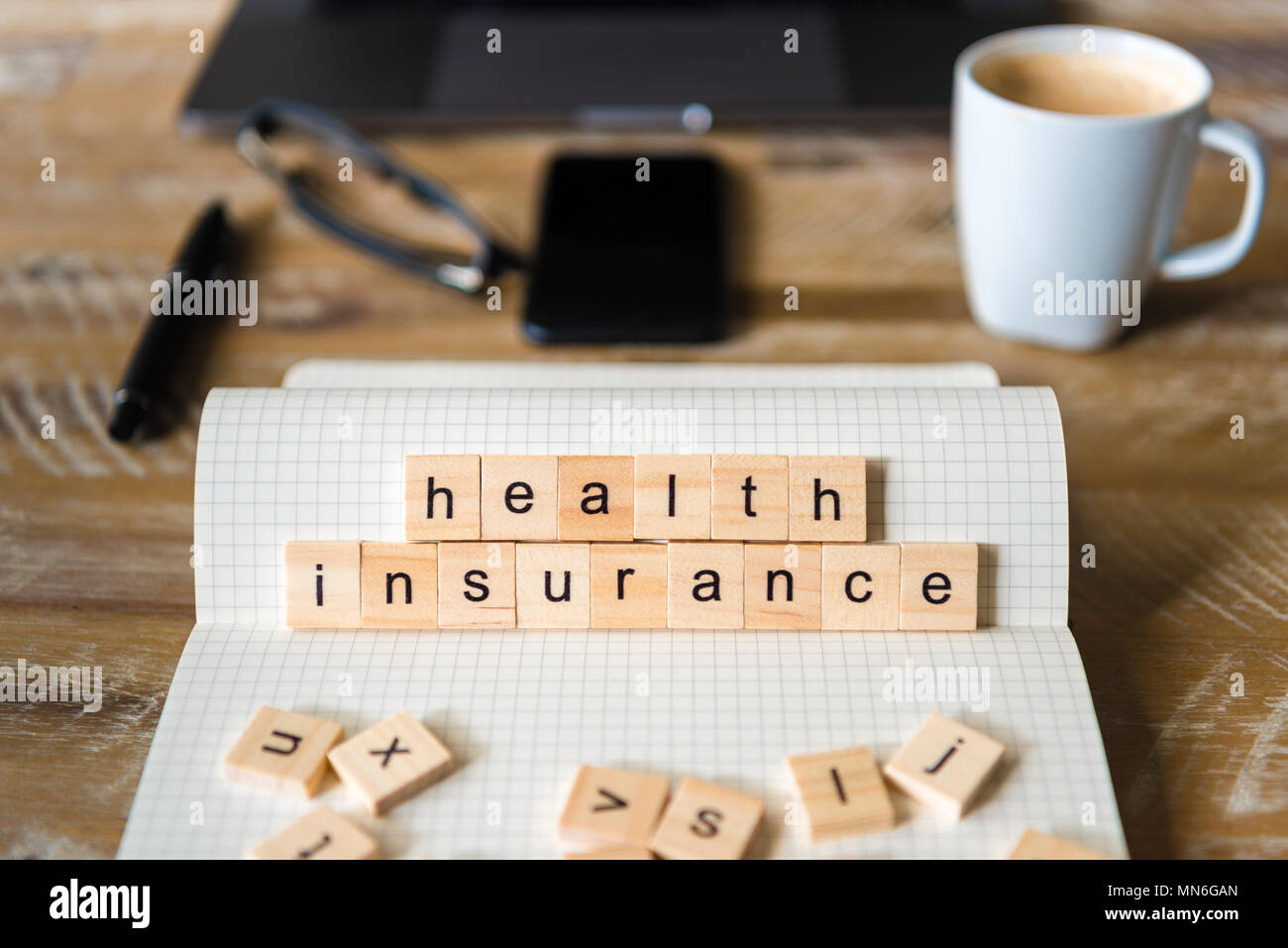 Nahaufnahme auf das Notebook um Holz Tisch Hintergrund, auf Holzblöcken mit Buchstaben, Krankenversicherung Worte konzentrieren. Stockbild