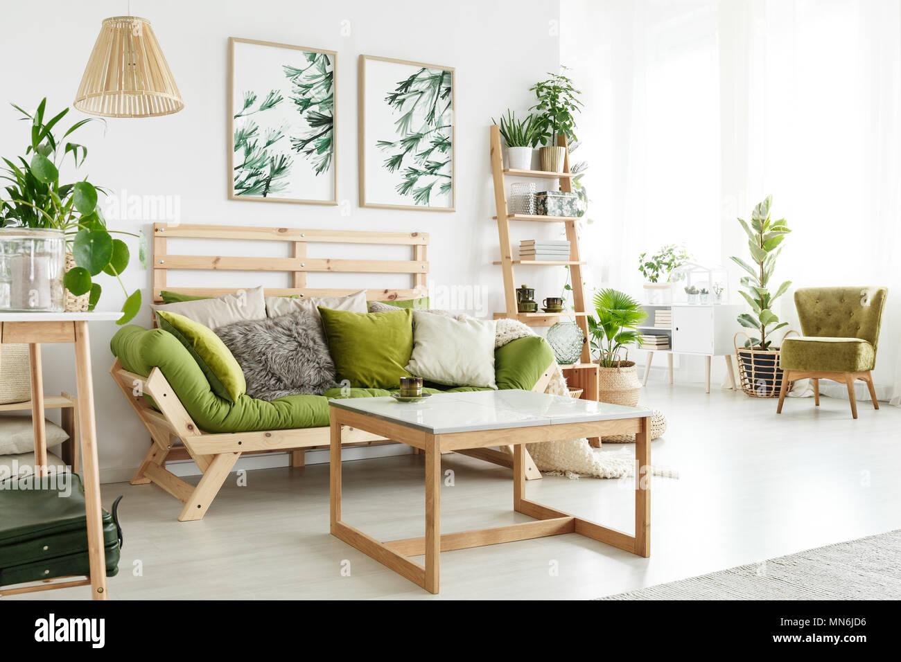 Holz- grüne Sofa mit Kissen gegen eine Wand mit Blättern ...
