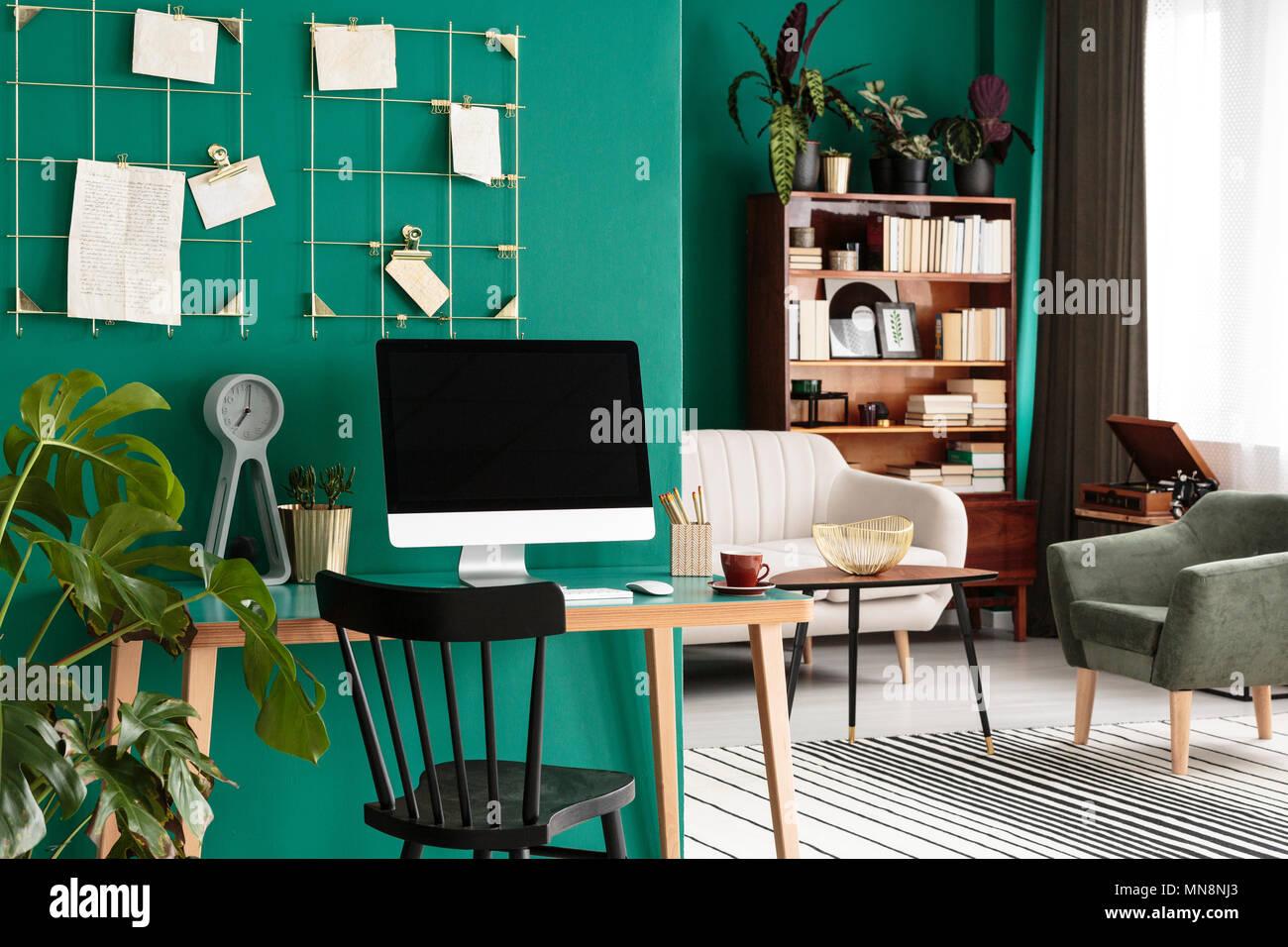 Neben einem hölzernen Stuhl mit Desktop Computer in grün Arbeitsbereich innen im offenen Wohnzimmer Stockbild