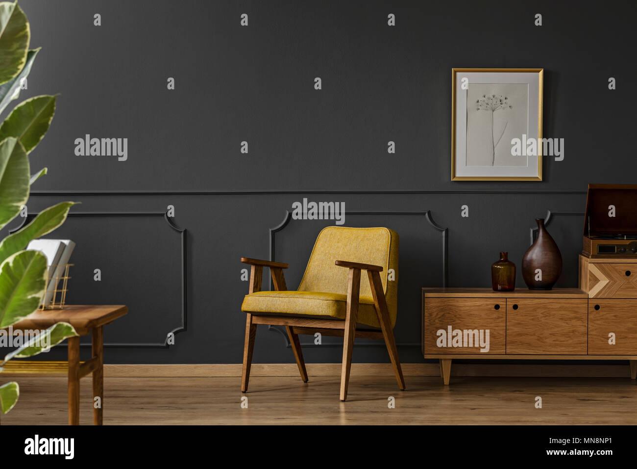 ein geraumiges vintage wohnzimmer einrichtung mit schwarzen wanden holzfussboden gelb stuhl poster und anlage