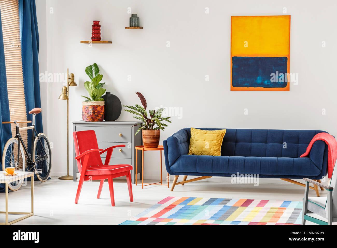 Red Chair Und Royal Blue Lounge Im Hellen Wohnzimmer Einrichtung Mit Bunten  Teppich, Moderne Kunst Malerei, Frische Pflanzen Und Gold Lampe Neben G
