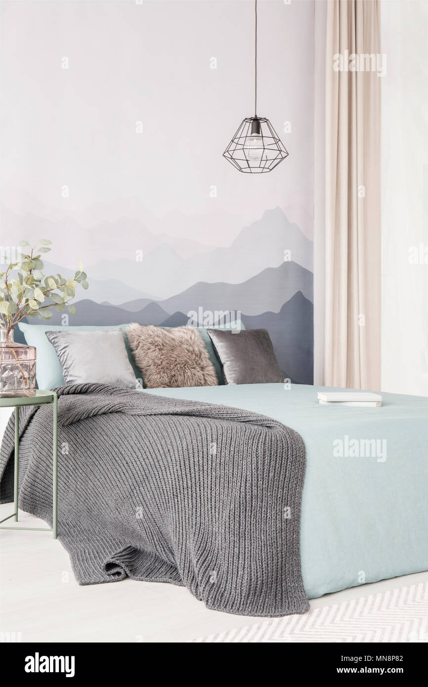 Lampe über dem grünen Bett mit grauen Decke im Schlafzimmer ...