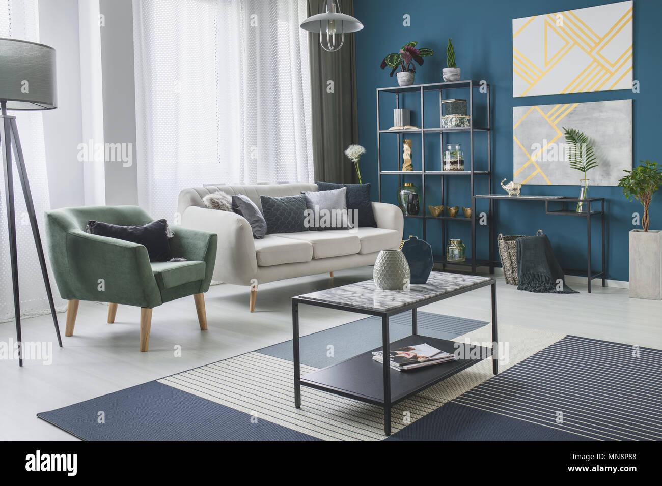 Grüne Sessel neben einem beige Sofa im Wohnzimmer Interieur mit gold ...