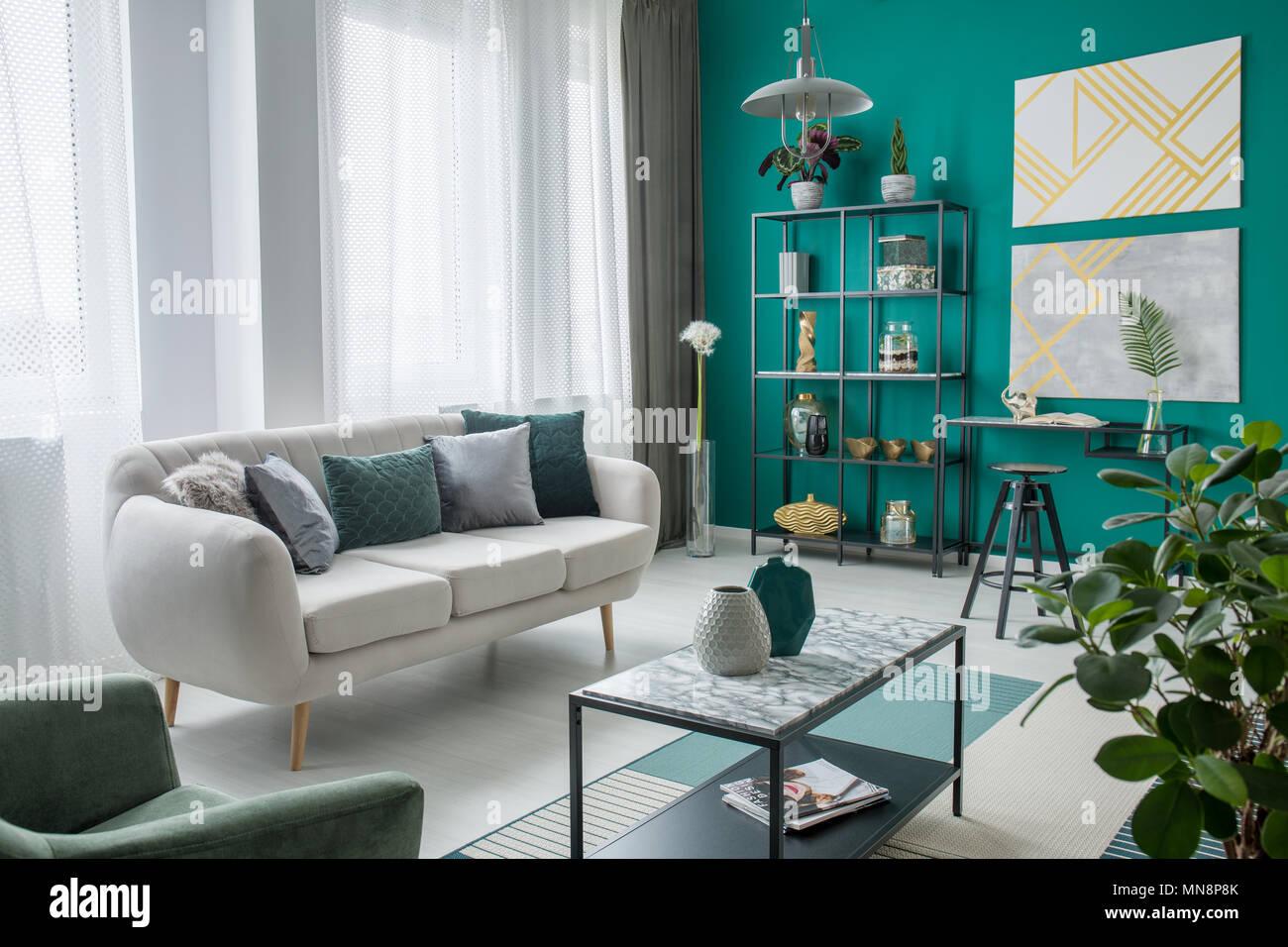 Beige Sofa im gemütlichen Wohnzimmer Interieur mit gold Gemälde auf ...