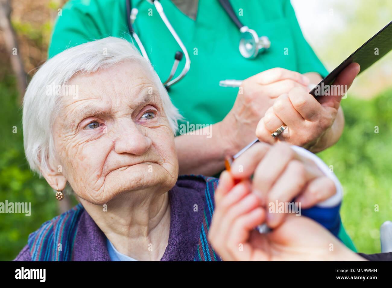 Ältere kranke Frau, die Pillen von Krankenschwester outdoor, Arzt schreiben ärztliche Verschreibung im Hintergrund Stockbild