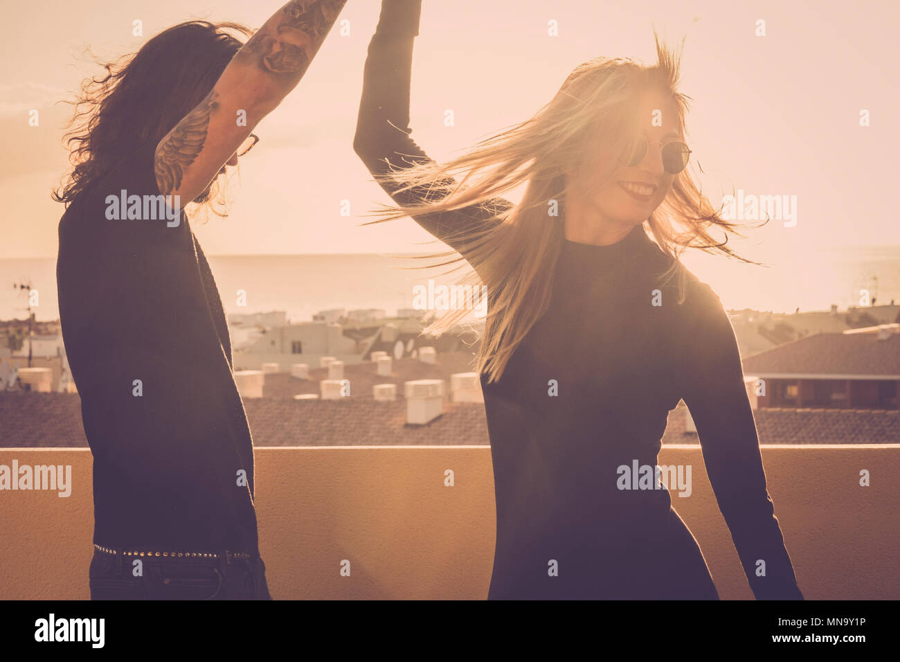 Schöne lange Haare jungen kaukasischen Paar tanzen und Bewegen auf der Dachterrasse mit Blick auf den Ozean. schönen Außenpool Sonne Licht und schöne Freizeitbeschäftigung auf Stockbild