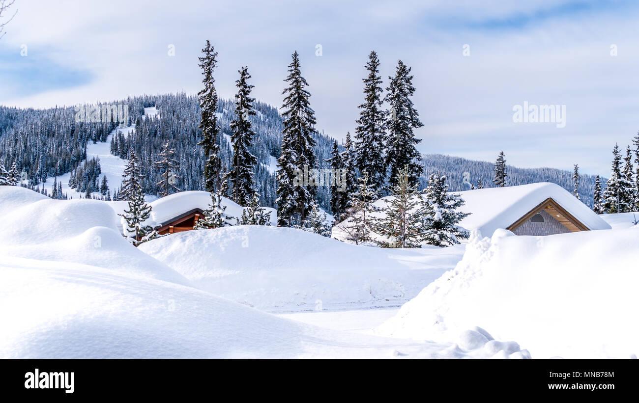 Schnee bedeckten Dächer der Häuser im Ski Village des berühmten Skigebiet Sun Peaks im wunderschönen British Columbia, Kanada Stockbild
