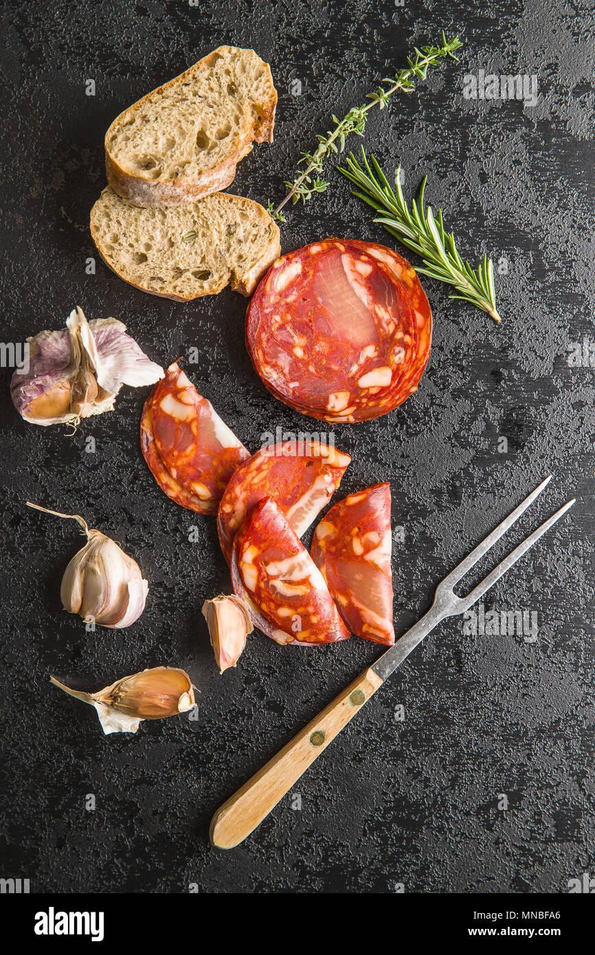 Scheiben Chorizo Salami Wurst, Knoblauch, Thymian, Rosmarin und Ciabatta Brot. Stockbild