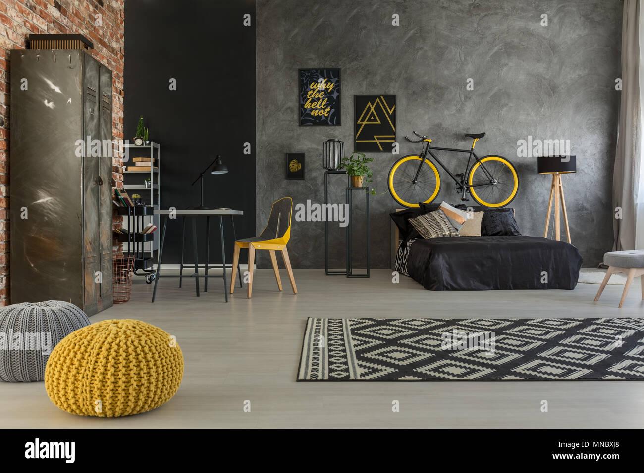 Grau Schlafzimmer mit Bett, Schreibtisch, Stuhl, Wand, gelb Details Stockbild