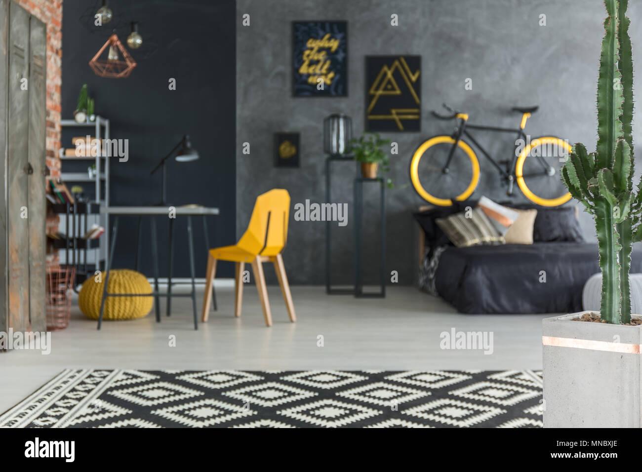 Grau hipster Zimmer mit Bett, Fahrrad, gelb Stuhl und Schreibtisch Stockbild