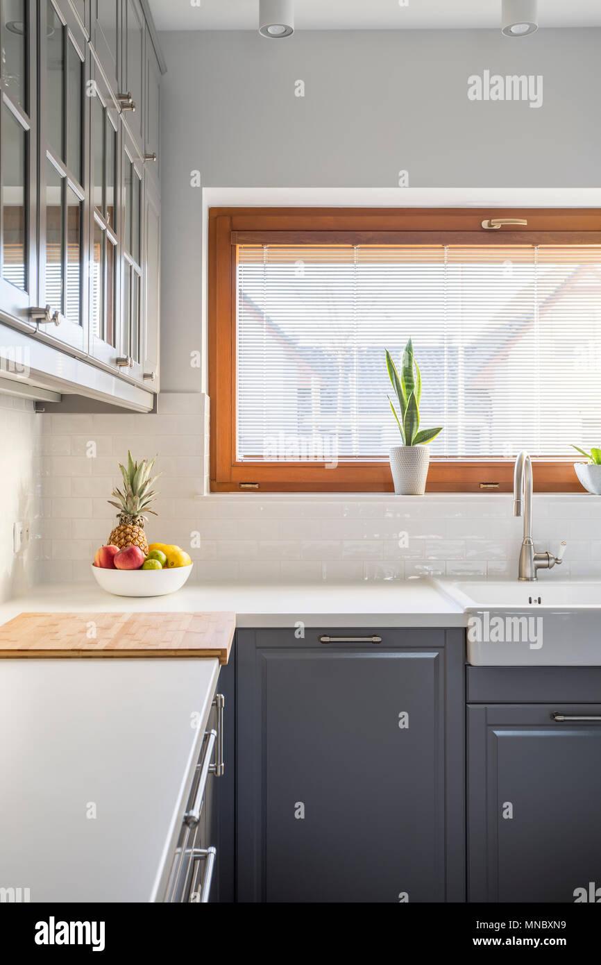 Moderne Küche mit Fenster, grau Küchenschrank, weiß Arbeitsplatte
