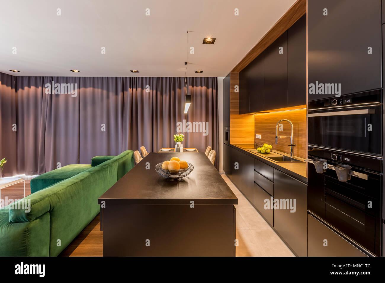 Kuche Insel In Dunklen Open Space Interieur Mit Grunen Couch Und Braunen Vorhangen Stockfotografie Alamy