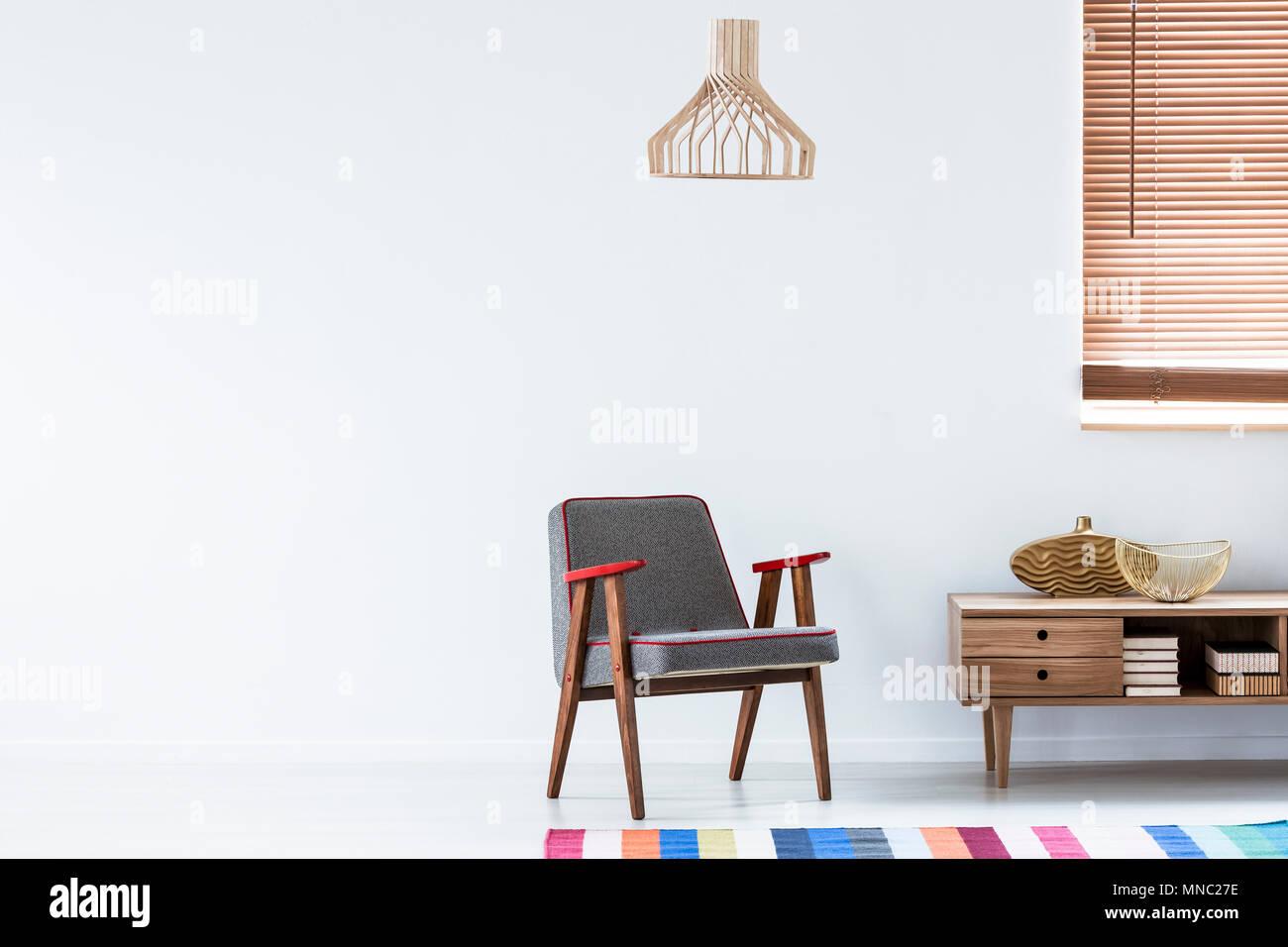 holz schrank wohnzimmer einrichtung, grau sessel neben einem holzschrank mit gold vase im gemütlichen, Design ideen
