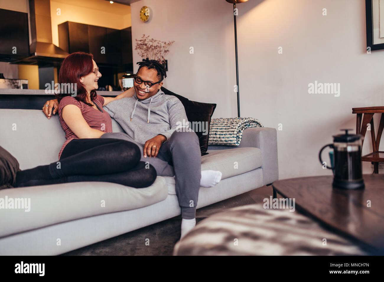Fröhliche Interracial Paare Sitzen Auf Einer Couch Im Wohnzimmer