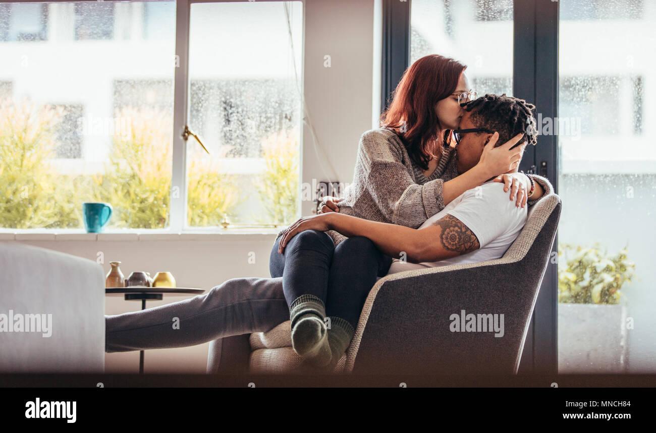 Frau küssen Freund Stirn mit Liebe, während auf einem Stuhl sitzen zusammen. Romantische interracial Paar zu Hause. Stockbild
