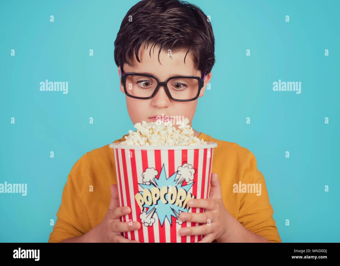 Kleiner Junge Kind mit Popcorn auf blauem Hintergrund Stockbild