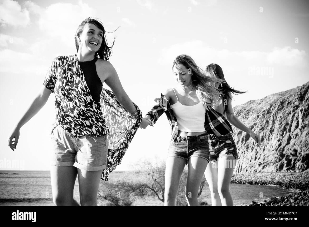 Drei junge Frauen, die Freunde gehen gemeinsam an einer Wand in der Nähe der Strand auf Teneriffa. Die Ferienhäuser unter einem blauen Himmel mit gelben Sonne genießen. Hände von den Händen. Stockbild