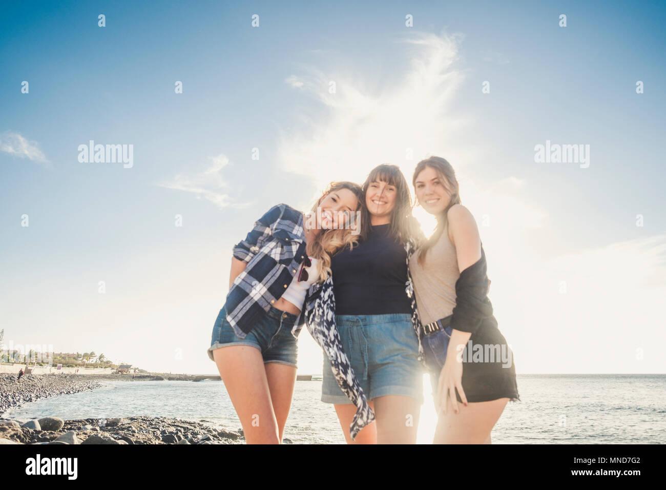 Gruppe von drei jungen Frau genießen Sie den Sommer auf einem Felsen am Strand auf Teneriffa, umarmen sich mit viel Lachen und Lächeln für ein perfektes Team Stockbild