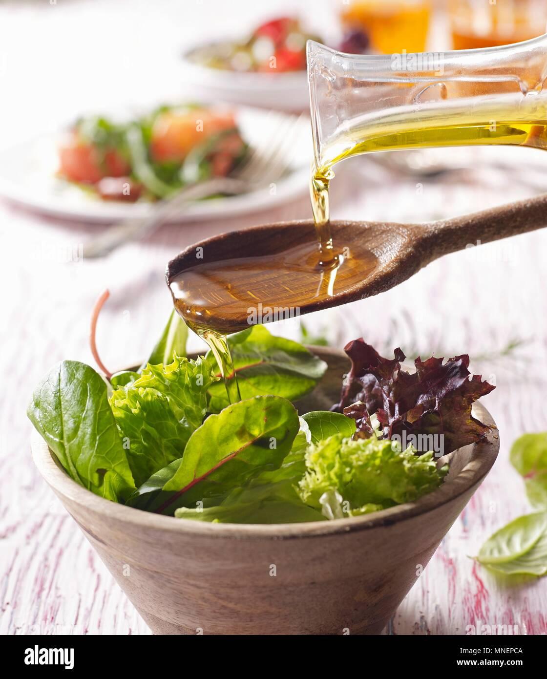 Öl wird über den Salat aus einem Holzlöffel offenporige Stockbild