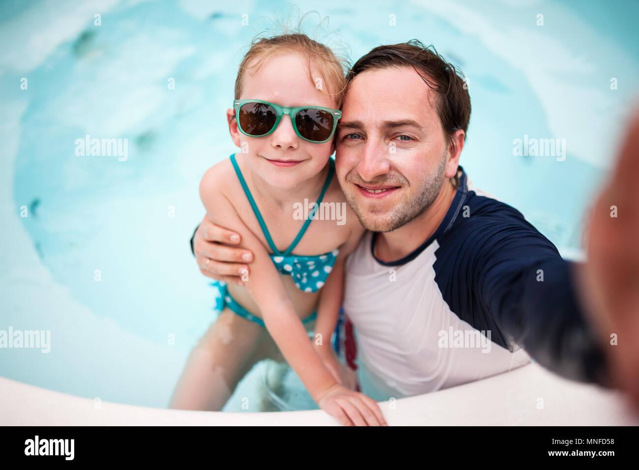 Glückliche Familie Vater und seine entzückende kleine Tochter im Swimmingpool im Freien, der die selfie Stockbild