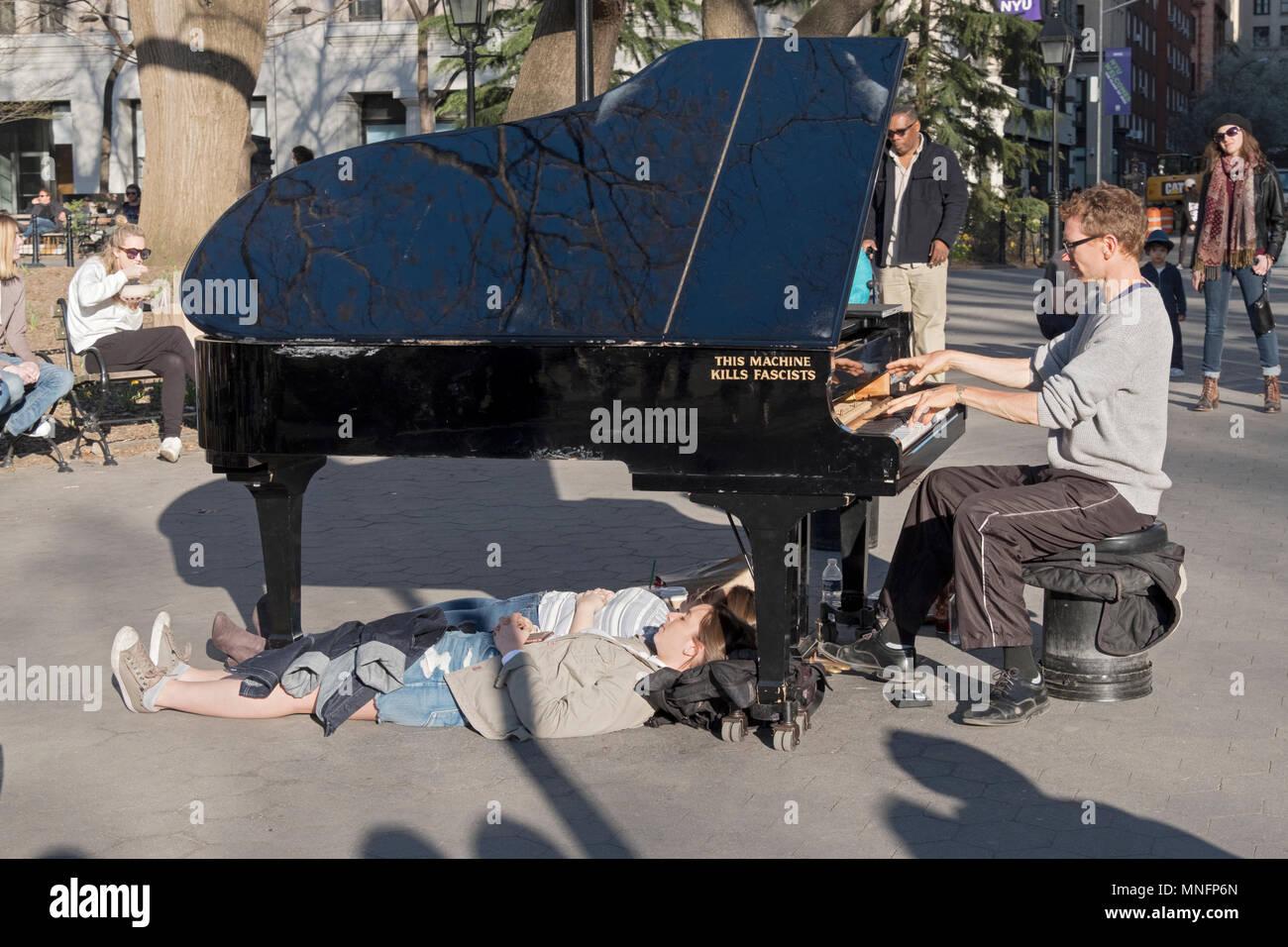 Ein strassenmusikant mit 2 Personen auf mysteriöse Weise unter seine Flügel liegen. Im Washington Square Park in Manhattan, New York City. Stockbild