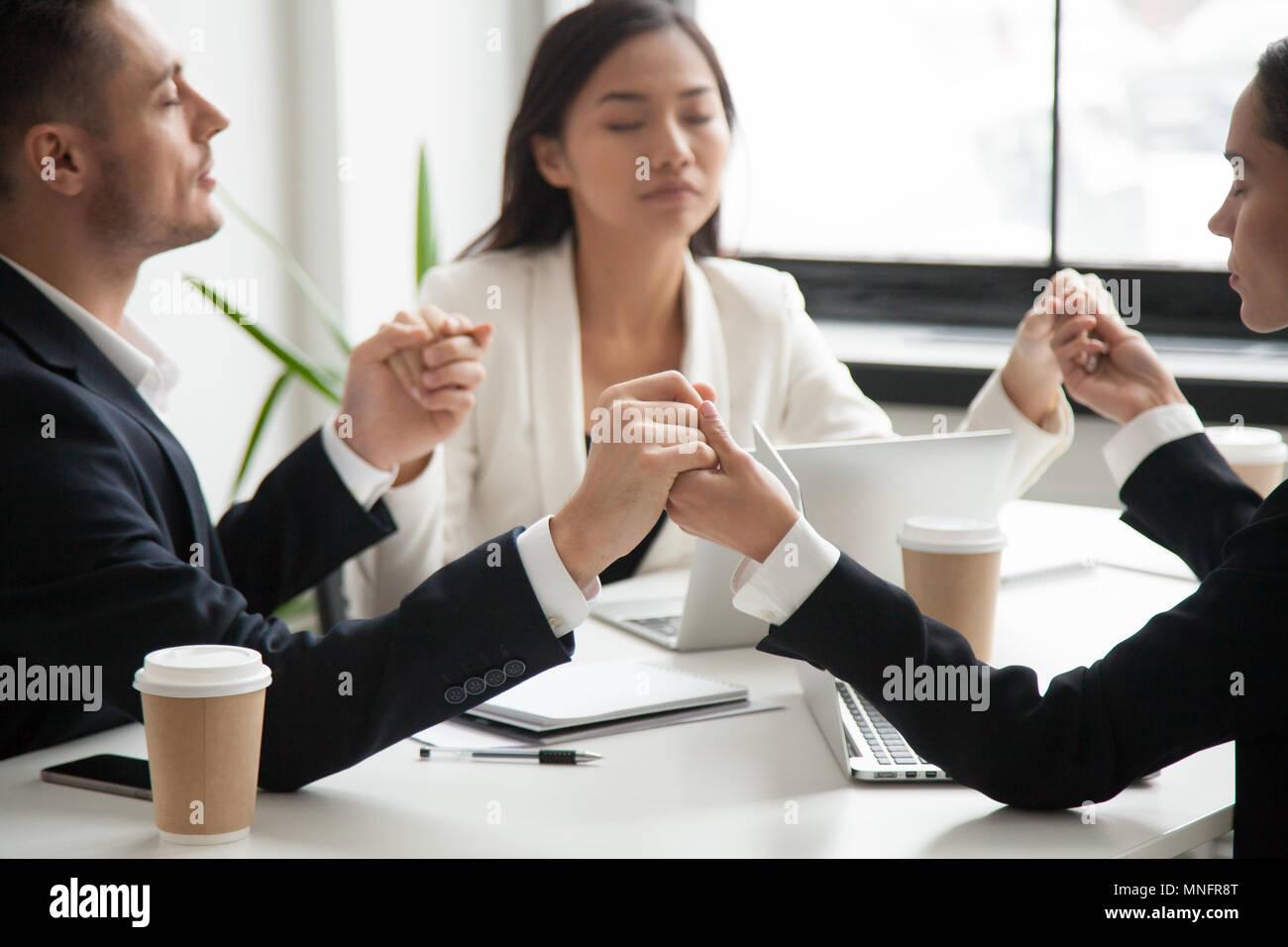 Business Team halten sich an den Händen und betet für den Erfolg Stockbild